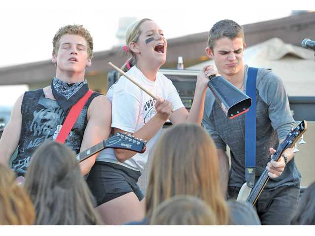 Canyon High School junior Julia Sloan, center, plays the cow bell after being called on stage by False Puppet at Canyon High on Friday.