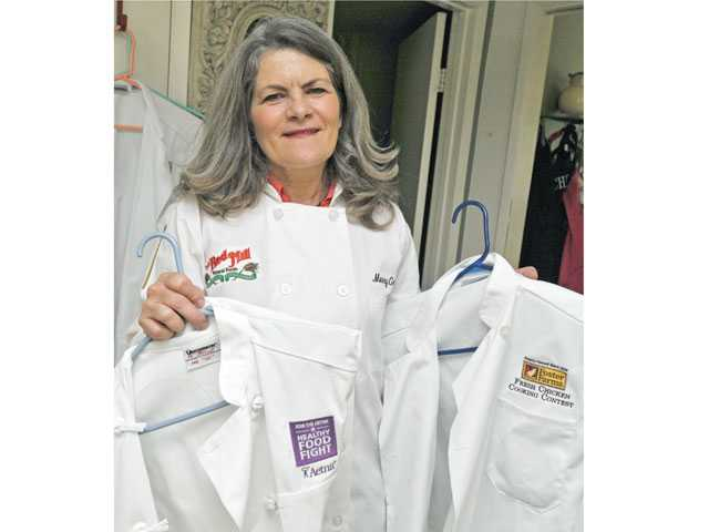 Merry Graham holds some of the chef jackets she has won by competing in recipe contests. Graham started competing in 2009 and has won thousands of dollars.