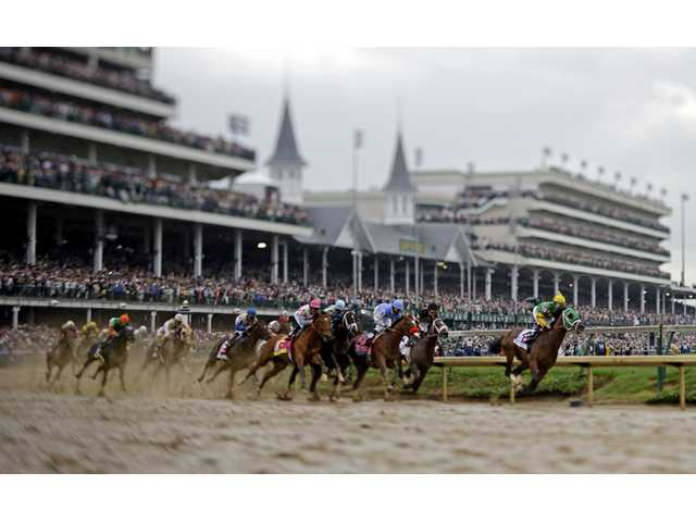 In this image made with a specialty lens, horses make their way around turn one during the 139th Kentucky Derby at Churchill Downs on Saturday in Louisville, Ky.