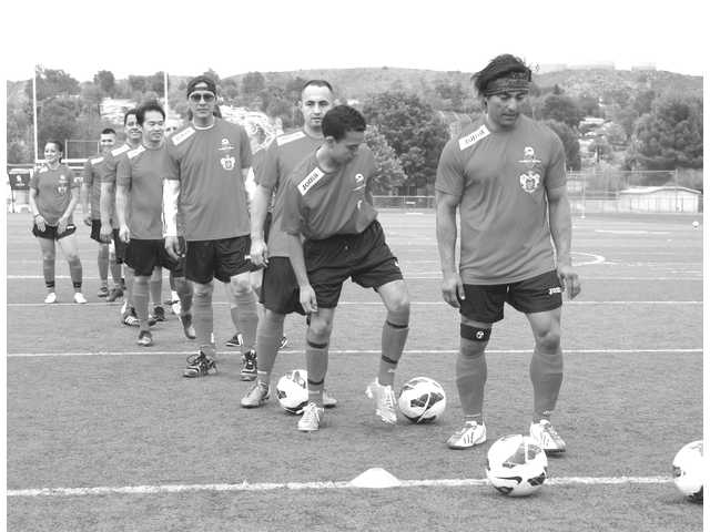 Players for the Combat Radio Celebrity Charity Soccer Invitational line up Sunday at Canyon High School.