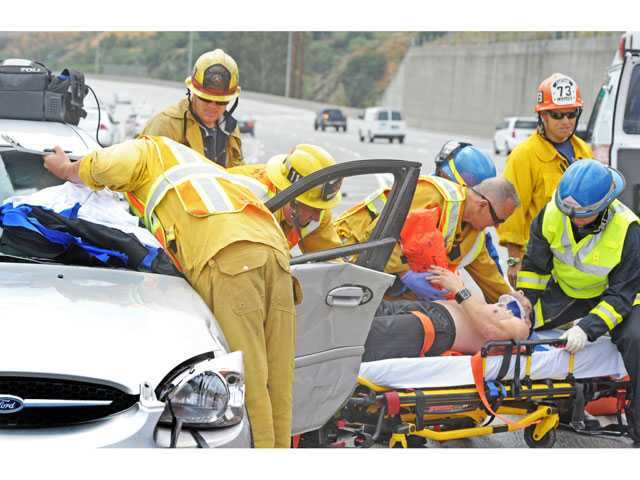 Firefighters and emergency medical technicians rescue a man pinned by a door of a Ford sedan involved in a 3-car collision on southbound Interstate 5 south of Highway 14 in Sylmar on Monday morning. (Jonathan Pobre/The Signal)