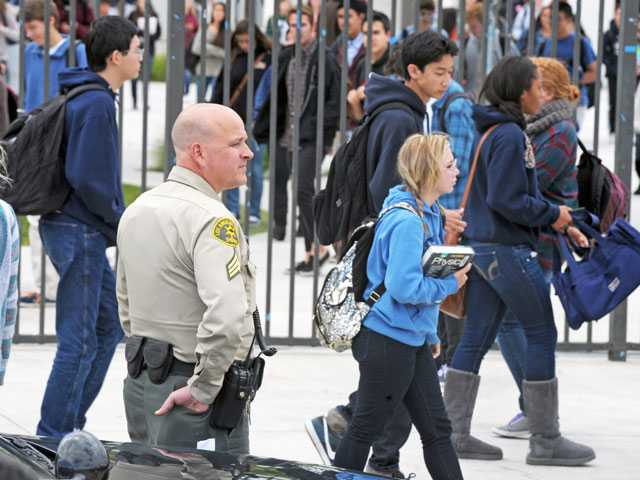 Sgt. Dan Stanley of the Santa Clarita Valley Sheriff's Station monitors the front gate as students are dismissed at West Ranch High School in Stevenson Ranch on Monday. (Jonathan Pobre/The Signal)