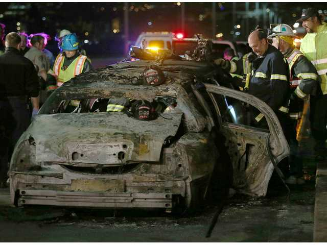 San Mateo County firefighters and California Highway Patrol personnel investigate the scene of a limousine fire in Foster City, Calif. on Saturday.