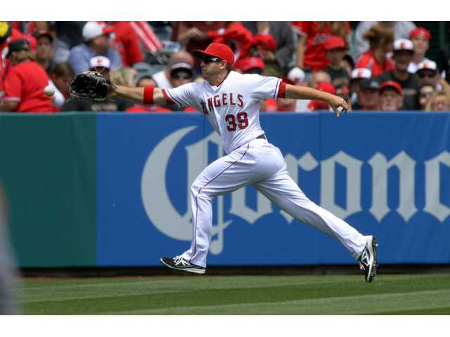 Los Angeles Angels left fielder J.B. Shuck can't reach a ball hit for a double by the Baltimore Orioles on Sunday in Anaheim.