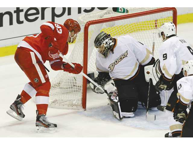 Detroit Red Wings left wing Johan Franzen, left, tries to score on Anaheim Ducks goalie Jonas Hiller, center, in Detroit on Monday.