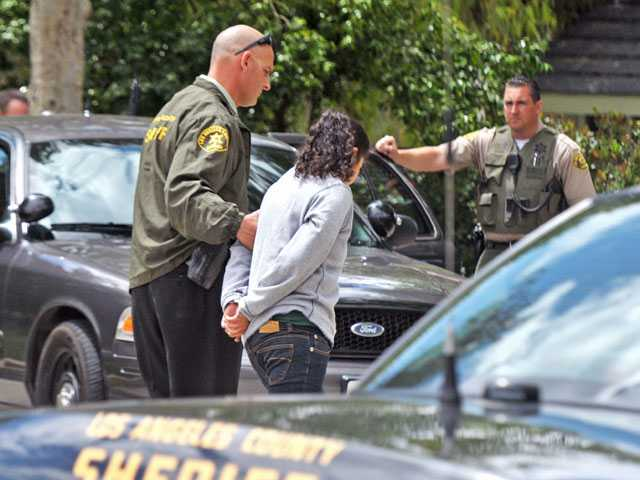 A Sheriff's Department detective leads a potential burglary suspect to a patrol vehicle after she is shown to witnesses on Cabezo Court in Valencia on Tuesday morning. (Jonathan Pobre/The Signal)