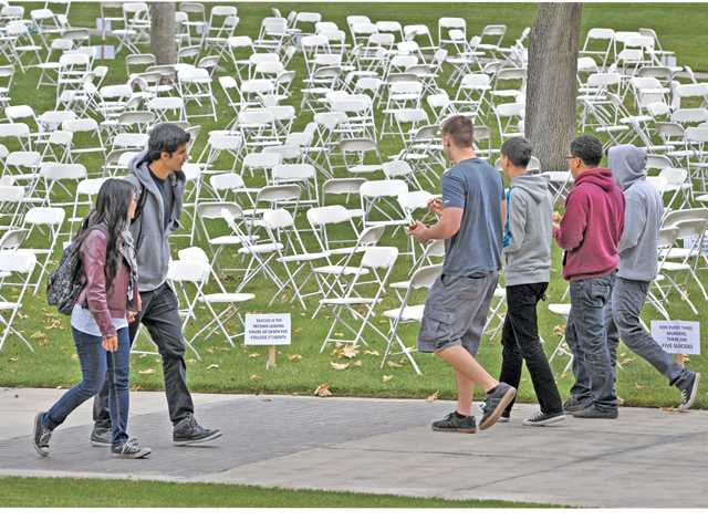 "Students walk along the path by 1,100 chairs set up on the College of the Canyons Valencia campus to acknowledge the average 1,100 college students per year who commit suicide in the U.S. The display was part of the college's ""Shine a Light on Sucide Prevention & Awareness"" event held today and Wednesday. Signal photo by Dan Watson"