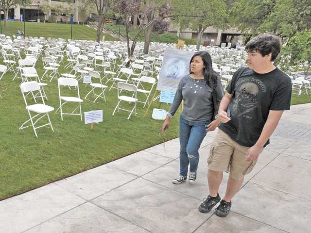 "Students Alexandra Guevara, left, and Bayley DeJong walk beside a College of the Canyons display illustrating the number of college students who commit suicide each year in the U.S. The display was part of a two-day ""Shine a Light on Suicide Prevention & Awareness"" event that continues Wednesday. Signal photo by Dan Watson"