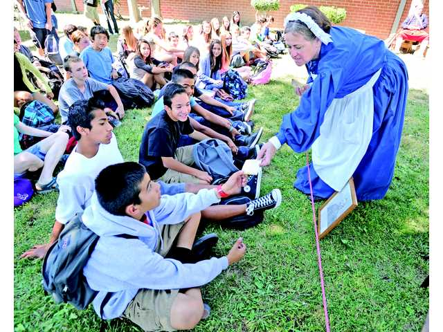 Lynn Johsz portrays a Civil War nurse as she hands out soldier's rations during a Civil War presentation at Placerita Canyon Junior High School on Friday. Signal photo by Dan Watson