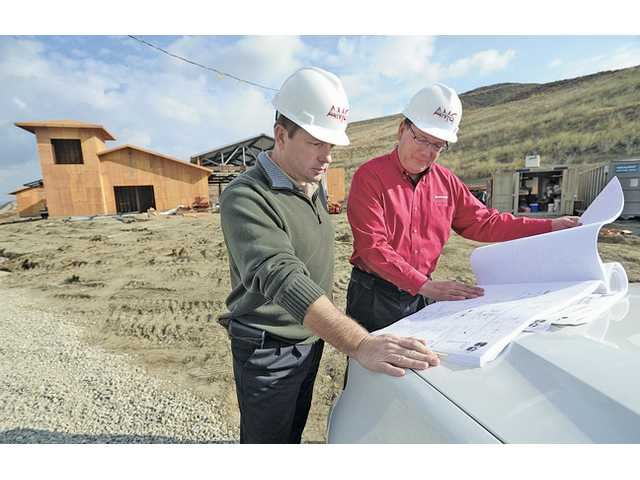 AMG & Associates co-owners Tony Traverso, left, and Albert Giacomazzi go over plans at the construction site of Fire Station 150 in Santa Clarita on Monday.