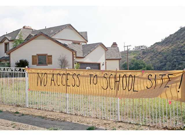 A sign hangs outside a house on Romero Canyon Road Wednesday. Romero Canyon residents set up several temporary roadblocks to protest the private road being used to get to the ceremony.