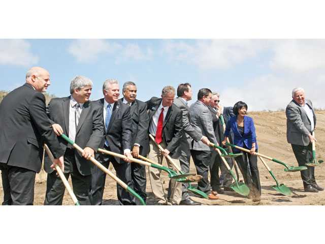 Officials take shovelfuls of dirt to mark the ceremonial groundbreaking for the Castaic High School project in Romero Canyon Wednesday morning. About 100 people attended the ceremony.