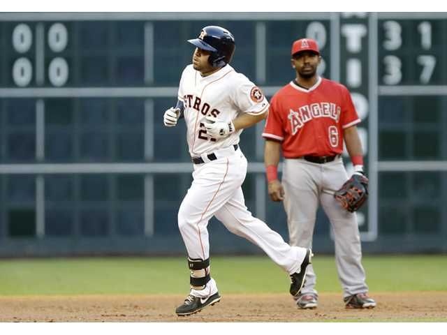 Houston Astros' Jose Altuve (27) passes Los Angeles Angel Alberto Callaspo (6) as he rounds the bases on a home run on Tuesday in Houston.
