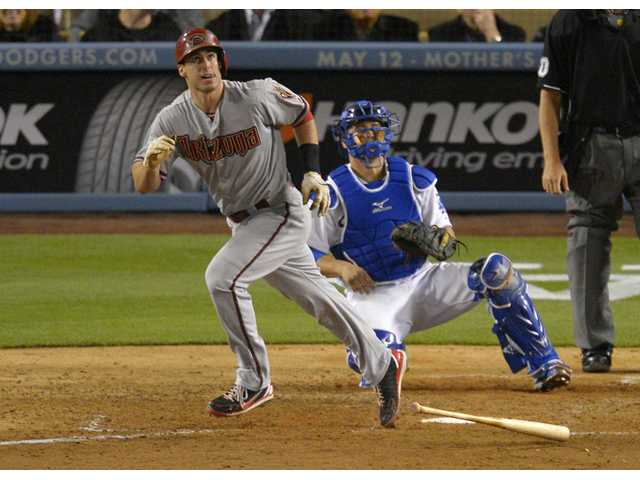 Arizona Diamondback Paul Goldschmidt, left, hits a home run as Los Angeles Dodgers catcher Ramon Hernandez looks on Tuesday in Los Angeles.