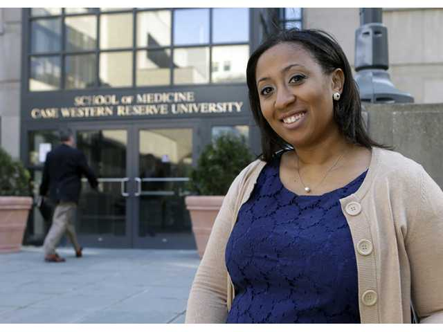 In this photo taken April 23, 2013, Lauren Howie, 27, poses outside the School of Medicine at Case Western Reserve University in Cleveland. America's blacks voted at a higher rate than other minority groups in 2012 and by most measures surpassed the white turnout for the first time, reflecting a deeply polarized presidential election in which blacks strongly supported Barack Obama while many whites stayed home.
