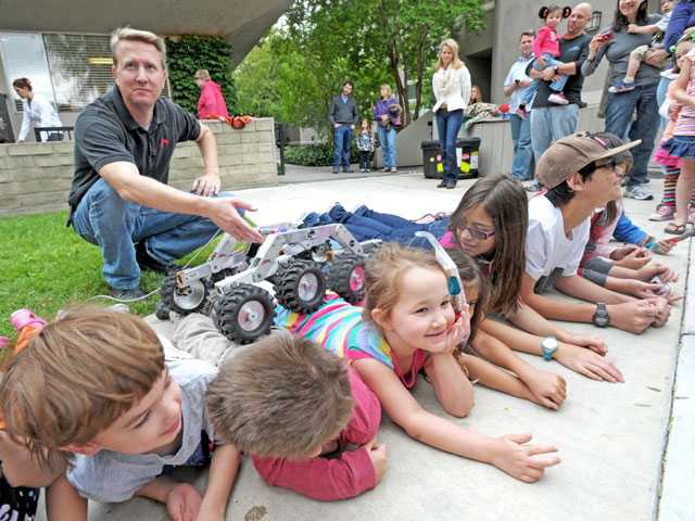 Chloe Judd, 5, center, reacts as Dennis Young, lead resource analyst on the Mars Science Laboratory, top left, guides a rover over her and fellow preschoolers to demonstrate how a rover navigates over rocks on Mars.