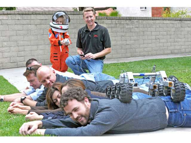 Madelyn Young, 4, standing left, and her father Dennis Young control a miniature rover over parent volunteers to demonstrate how a rover navigates over rocks on Mars.