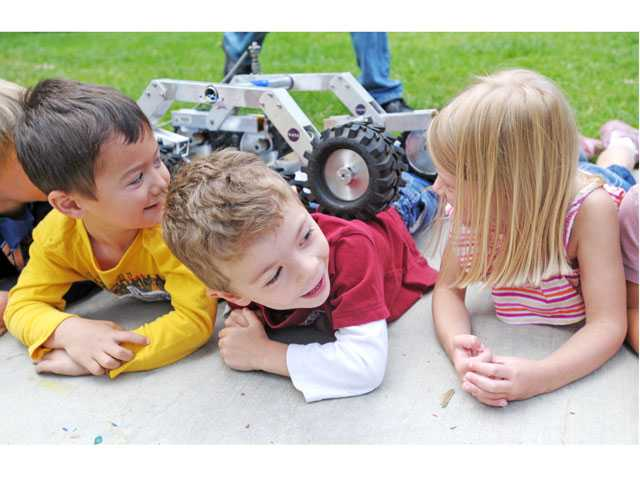 From left, Matthew Albin, 4, Justin Yamamoto, 3, and Hannah Langan, 3, laugh as a minature rover rolls over them in a demonstration of how the Mars rover Curiosity navigate over rocks on Mars.