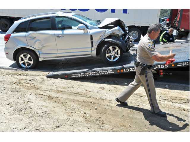 A California Highway Patrol officer walks past one of the vehicles involved in a multi-car crash on the northbound Interstate 5 near Calgrove Boulevard in Newhall on Friday. Signal photo by Jonathan Pobre