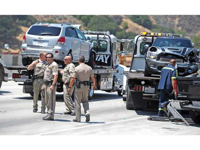 California Highway Patrol officers examine the scene of a nine-vehicle crash in Newhall on Friday as tow truck drivers load damaged vehicles onto trucks. Seven people were injured in the crash. Signal photo by Jonathan Pobre