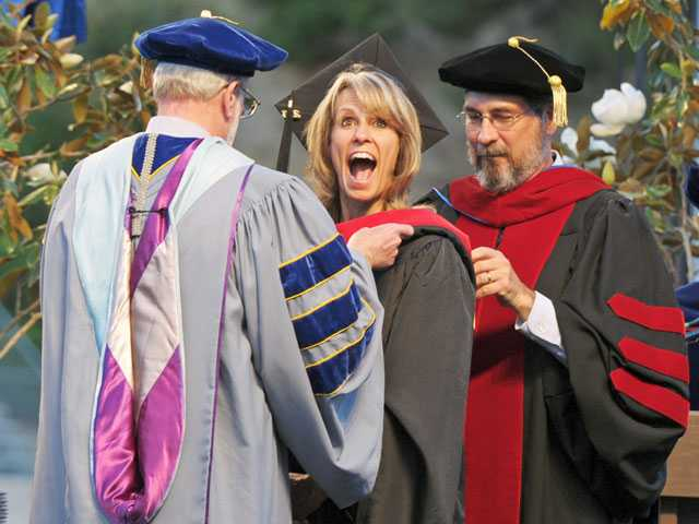 The Master's College graduate Carrie Foldberg, middle, expresses excitement as Biblical Studies chair Thomas Halstead, left, and faculty member Ernie Baker award her a degree on Friday at College of the Canyons.