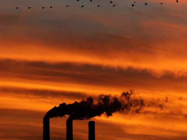 In this Sunday, Dec. 2, 2012 photo, a flock of Geese fly past the smokestacks at the Jeffrey Energy Center coal power plant as the suns sets near Emmett, Kan. Worldwide levels of the chief greenhouse gas that causes global warming have hit a milestone, reaching an amount never before encountered by humans, federal scientists said Friday, May 10, 2013.