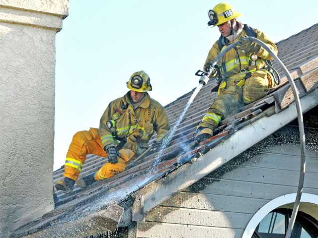 Firefighters douse the smoldering roof of a house on the 27000 block of Saddleridge Way in Castaic on Saturday. Signal photo by Jonathan Pobre