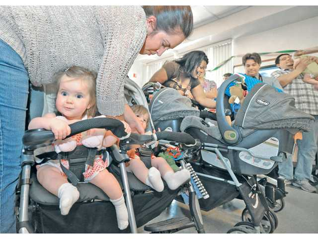 Mom, Erin Finn buckles in her 10-month-old twins Kylie, left, and Dylan as she prepares to speak at the NICU Reunion Program held at Henry Mayo Newhall Memorial Hospital on May 2. Photo by Dan Watson