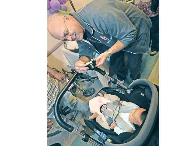 Respiratory therapist Joe Correnti takes a photo of four month old Jacob Tsao at the NICU Reunion Program held at Henry Mayo Newhall Memorial Hospital on Thursday. Correnti was there at the birth of Jacob. Photo by Dan Watson