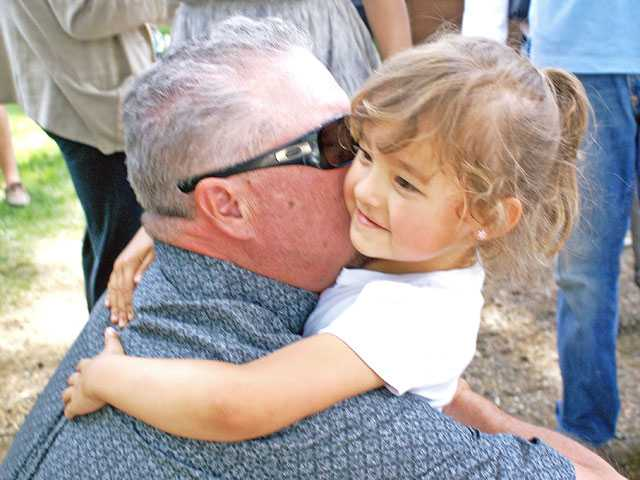 Brittany Schlumpberger's father, Kevin, gets a hug from Alexa Hackman on Saturday. More than 200 people turned out to celebrate the life of Brittany Schlumpberger killed in a single-car crash May 1.