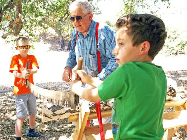 Sampling a bit of history first hand at the Placerita Canyon Nature Center's Open House Saturday, Caleb Hoyle (left) and Eric Provencio use a two-man saw as Al Wallander looks on.