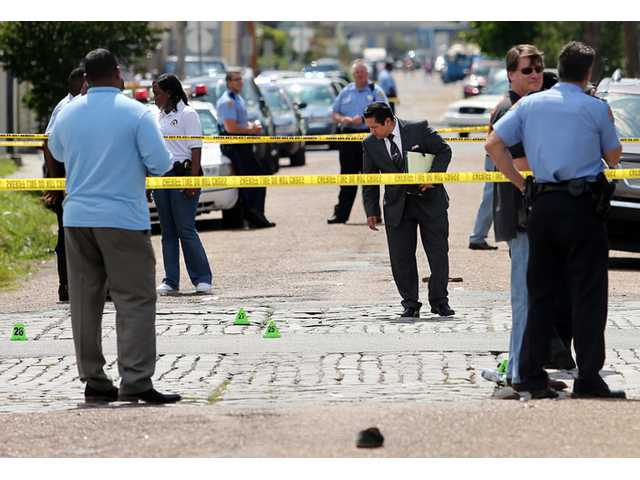 New Orleans police officers investigate the scene in New Orleans after gunfire at a Mother's Day second-line parade on Sunday. Police reported 17 people were injured and most of the wounds weren't life-threatening. No deaths were reported.