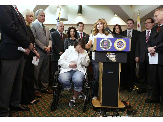 In this March 19, 2013 file photo, Brandy Arreola, seated, who was permanently injured last year by her boyfriend, a parole violator who had been released early from jail because of overcrowding, holds her head in her hands as her mother, Diana Munoz, discusses the attack during a news conference at the Capitol in Sacramento, Calif.