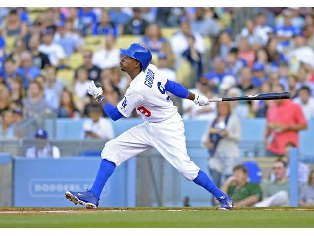 Los Angeles Dodger Dee Gordon hits a solo home run against the Miami Marlins on Saturday in Los Angeles.