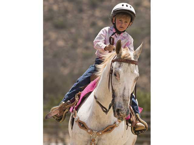 Faith Scott leads her horse around one of the barrels in the Peewee Barrel Racing event during the Antelope Valley Youth Rodeo Association junoir rodeo on Sunday at JPK Arena in Agua Dulce. Photo by Steve Palma