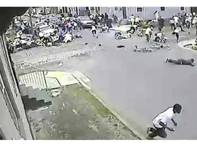 In this image taken from video provided Monday by the New Orleans Police Department, a possible shooting suspect in a white shirt, bottom center, shoots into a crowd of people, Sunday in New Orleans.