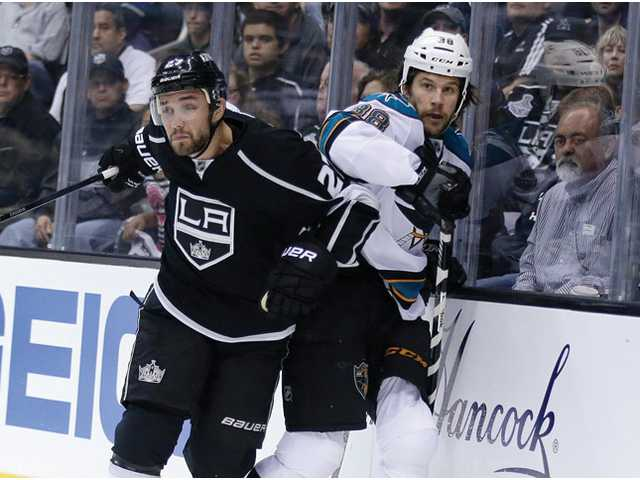 Los Angeles King Alec Martinez, left, keeps San Jose Shark Bracken Kearns against the boards in Los Angeles on Tuesday.