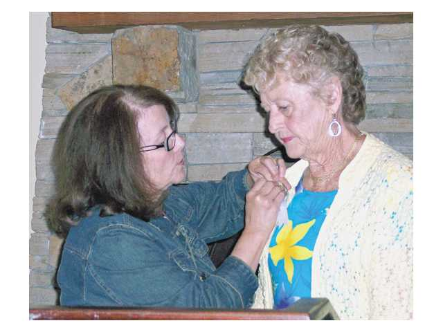 "Evie Leslie receives a pin from Mary Ellen Frye after Leslie was named ""Girl of the Year"" by Xi Nu Zeta."