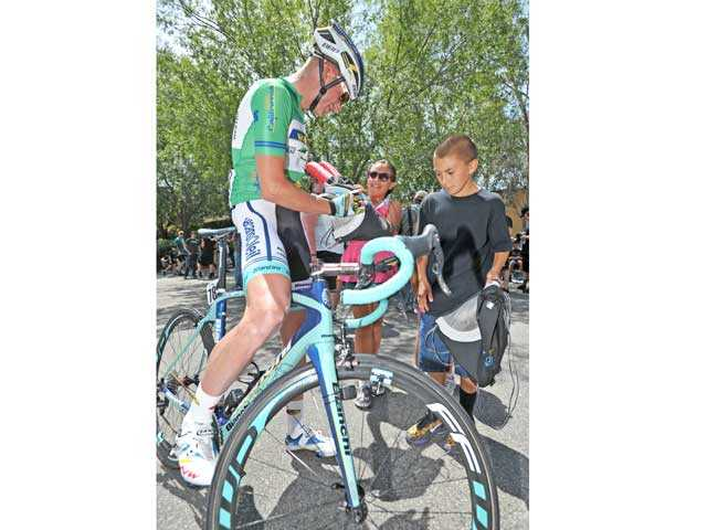 From left, Dutch cyclist Lieuwe Westra signs autographs for siblings Danielle, 9, and Tyler McNeil of Valencia. Signal photo by Jonathan Pobre