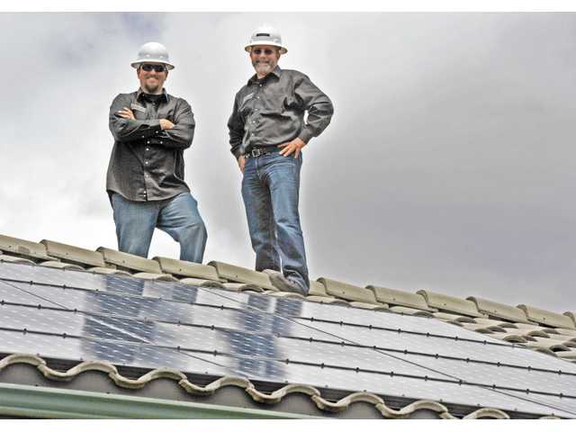 Project manager Ken Scherer, left, and CEO Mark Figearo of SunPower by Green Convergence pose atop a Stevenson Ranch home which recently had solar panels installed. Photo by Jonathan Pobre
