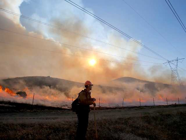 A firefightier watches a backfire set in Hungry Valley State Park to halt the prgress of the Grand fire, which charred more than 3,500 acres of wildlands near Frazier Park on Wednesday. Los Angeles Times photo