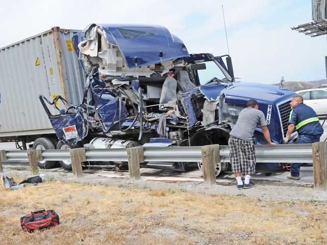 The driver of a big rig truck, left, stands next to the damaged cab of his truck as a tow truck driver prepares to move it off the southbound lanes Interstate 5 where it collided with another truck near the Hasley Canyon Road exit in Castaic on Thursday. Signal photo by Dan Watson