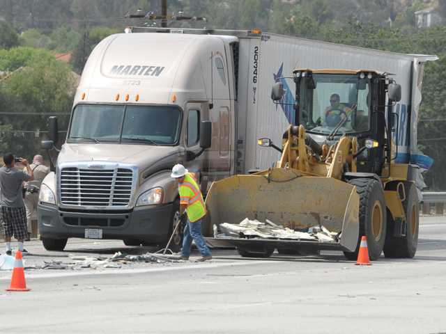 Caltrans workers use a skip-loader to remove debris from the roadway after two big rig trucks collided on the southbound Interstate 5 near the Hasley Canyon Road exit in Castaic on Thursday. Signal photo by Dan Watson