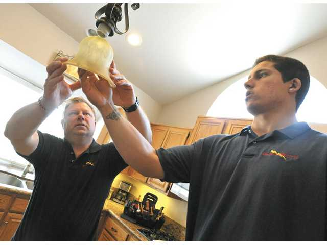 Randy Deckers, left, and son James Deckers of Deckers Electric assemble a light fixture in a Saugus home. Strong gains in homeowner remodeling are expected this year.