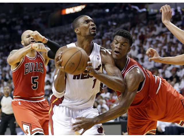 Miami Heat's Chris Bosh (1) drives to the basket as Chicago Bulls' Jimmy Butler, right, defends on Wednesday in Miami.