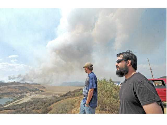 Mike Whitaker, left, and Andrew Fullingim of Castaic watch smoke from the Castaic brush fire on Friday. Signal photo by Jonathan Pobre