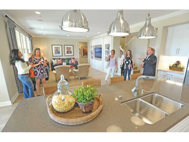 Tom DiPrima of KB homes, right, gives a tour of the great room of Residence 2 on Friday.