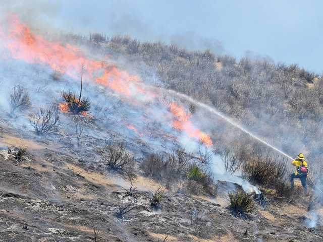 Firefighters spray water on the Castaic blaze as it moves up an embankment near its point of origin on the Interstate 5 freeway. Signal photo by Dan Watson