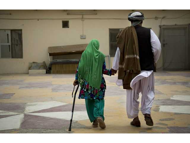 Zardana, 11, holds the hand of her father, Samiullah, after an interview in Kandahar, Afghanistan on Monday. Surviving family members recalled how a U.S. soldier attacked their home on March 11, 2012, shooting Zardana in the head.