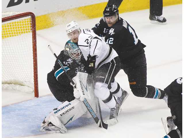 Los Angeles Kings center Trevor Lewis (22) collides with San Jose Sharks goalie Antti Niemi (31) on Saturday in San Jose.